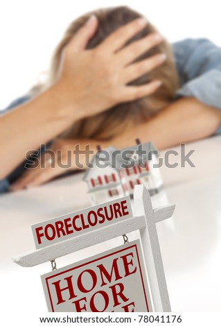 Woman with Head in Hand Behind Model Home and Foreclosure Real Estate Sign in Front. - stock photo