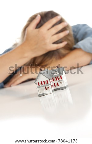 Woman with Head in Hand Behind Model Home on a White Surface. - stock photo