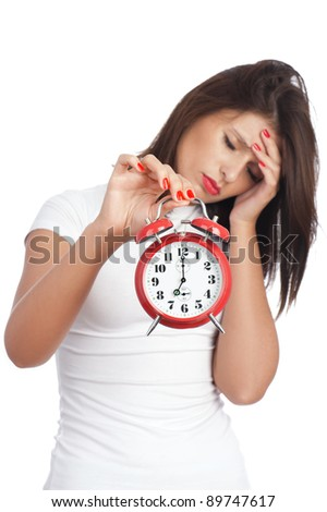 Woman with headache holding red alarm clock isolated on white background. Shallow DOF, focus is on alarm clock. Conceptual image - woman under pressure.