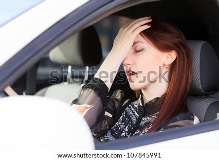 Woman with headache in a car - stock photo