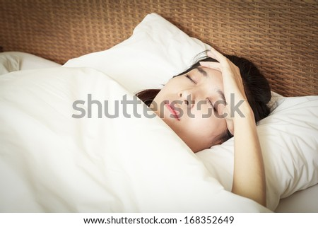 woman with headache lying on bed - stock photo