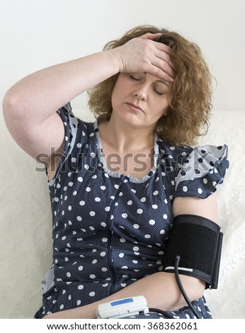Woman with headache measures the blood pressure