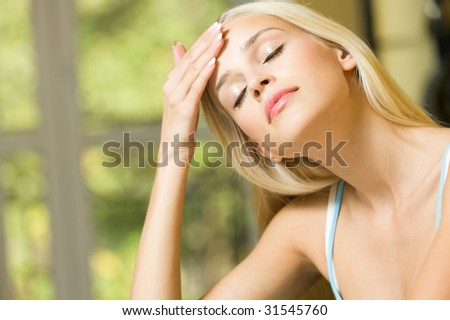 Woman with headache or applying cream on face at home