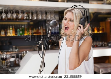 Woman with headphone singing while closing her eyes at the nightclub - stock photo