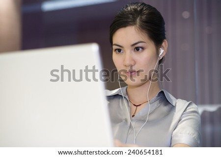 Woman with Headphones Working at Computer