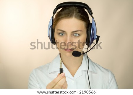 Woman with headset and microphone discovering she´s unplugged - stock photo