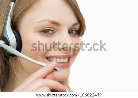 Woman with headset smiling against a white background - stock photo