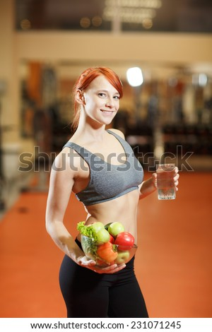 woman with healthy sporty figure holding vegetables - stock photo
