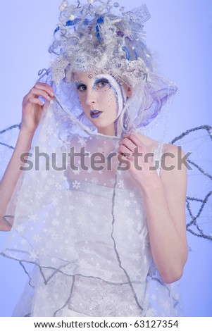 Woman with heavy stage makeup looking like a winter fairy. - stock photo