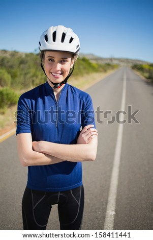 Woman with helmet crossing arms looking at camera - stock photo