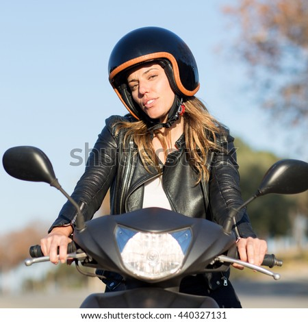 Woman with helmet on motor bike driving