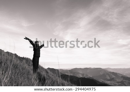Woman with her arms out stretched enjoying the view. - stock photo
