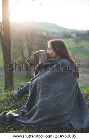 Woman with her beautiful dog lying outdoors, watching sunset  - stock photo