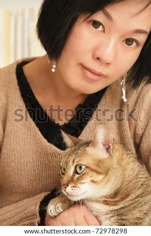 Woman with her cat of pet in home and looking at you.