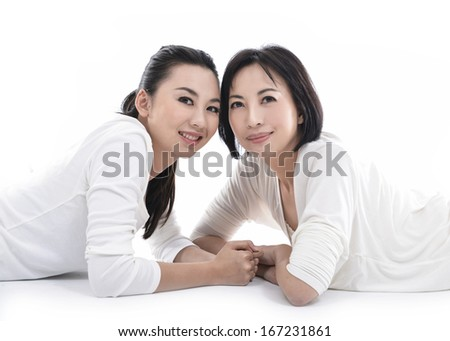 woman with her daughter lying on isolated over white background - stock photo