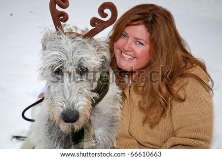 woman with her dog in the snow - stock photo