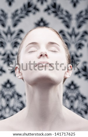 Woman with her eyes closed with very pale skin looking up. - stock photo