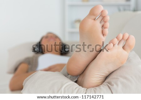 Woman with her feet up listening to music on the sofa - stock photo