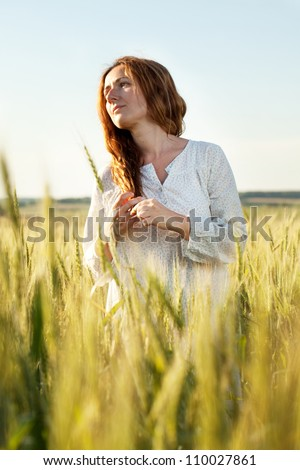 Woman with her hair down the middle of a wheat field