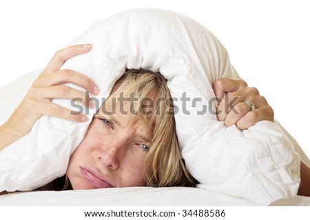 Woman with her head under her pillow trying to sleep - stock photo