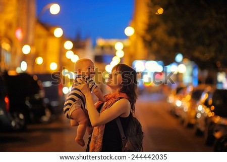 Woman with her little baby walking at the night city - stock photo