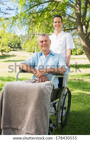 Woman with her mature father sitting in wheel chair at the park