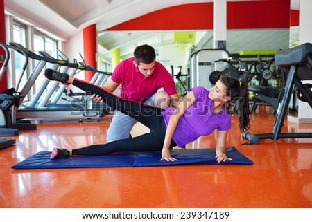 Woman with her personal fitness trainer in the gym - stock photo