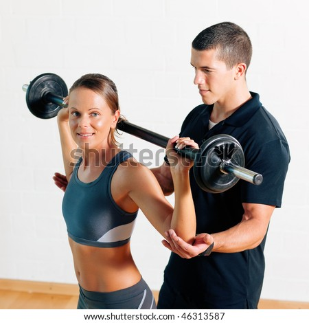 Woman with her personal fitness trainer in the gym exercising power gymnastics with a barbell - stock photo
