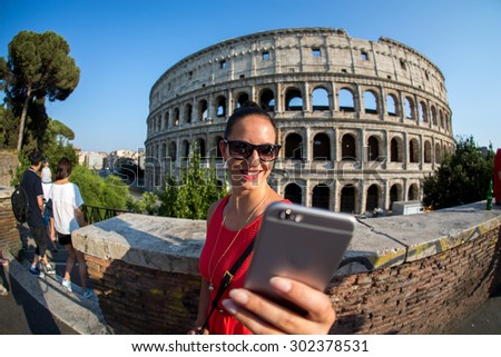 Woman with her smartphone in front of the colosseum in roma - stock photo