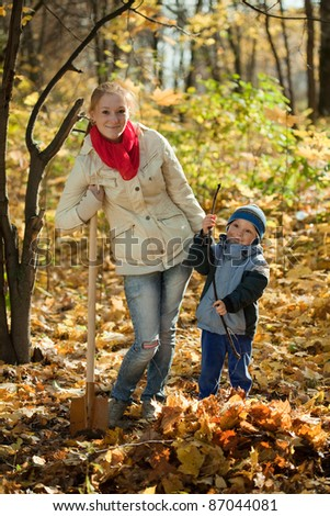 woman with her son working with spade in autumn - stock photo