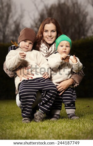 Woman with her sons in home garden - stock photo