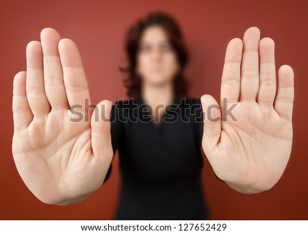Woman with her two hands extended signaling to stop (only her hands are in focus) on a red background