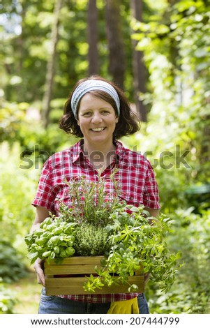 woman with herbs in a garden - stock photo