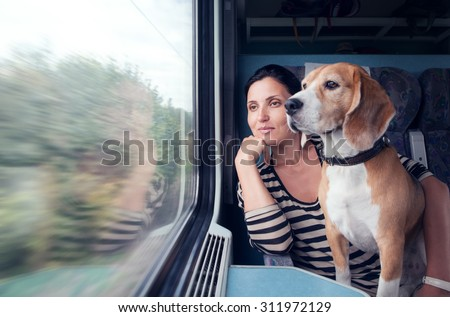Woman with his dog travel in railway wagon - stock photo