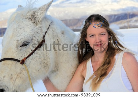 Woman with horse in snow - stock photo