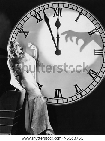 Woman with huge clock recoiling from frightening hand - stock photo