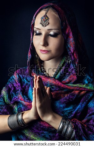 Woman with Indian tikka wrapped in scarf doing Namaste mudra at dark background  - stock photo