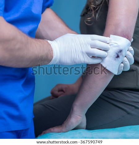 Woman with injured elbow in treatment room - stock photo