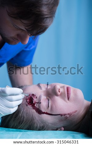 Woman with injured head in emergency room - stock photo