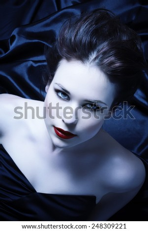 Woman with intense stare laying on black silk sheets. - stock photo