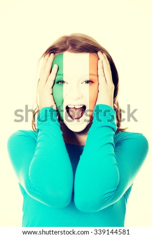 Woman with Ireland flag painted on face. - stock photo