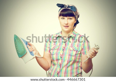 Woman with iron in her hand isolated on a white background. - stock photo