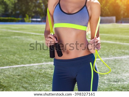 Woman with jumping rope. Beautiful young woman standing with a jumping rope in her hands with a stadium as background - stock photo