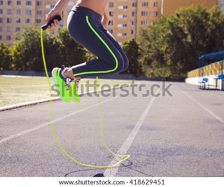 Woman with jumping rope. Beautiful young woman with a jumping rope in her hands with a stadium as background. Close up