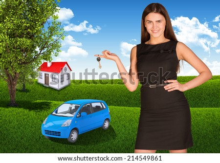 Woman with key in hand. Small automobile and house on grass - stock photo