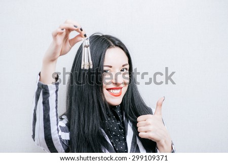 Woman with keys showing thumb up. On a gray background. - stock photo