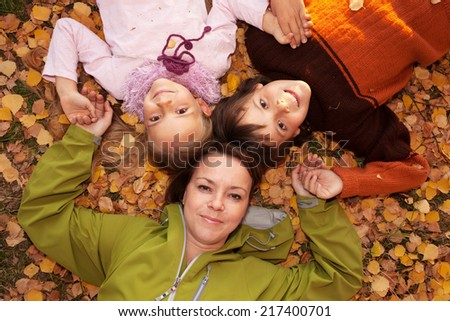 Woman with kids laying on the autumn ground covered with yellow leaves - stock photo