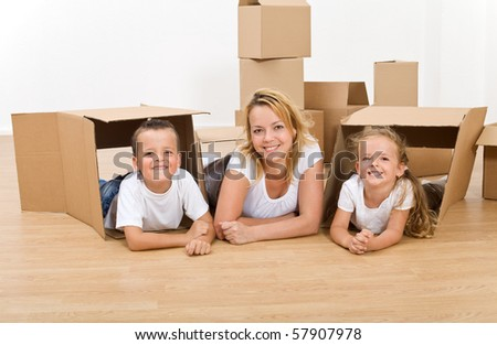 Woman with kids playing in their new home with cardboard boxes - stock photo
