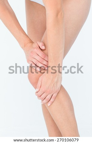 Woman with knee pain on white background - stock photo