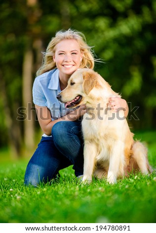 Woman with labrador sitting on the green grass in the summer park - stock photo